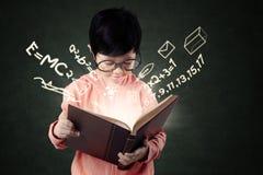La ragazza sveglia legge un libro di scienza Fotografia Stock