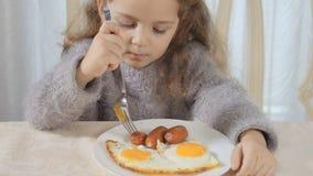 La ragazza sveglia mangia la salsiccia con la forcella stock footage
