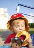 La ragazza sveglia mangia un bagel Fotografia Stock Libera da Diritti
