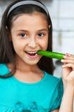 La ragazza sveglia mangia un pepe Immagine Stock