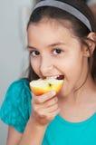 La ragazza sveglia mangia una mela Fotografia Stock Libera da Diritti