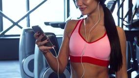 La ragazza sveglia scrive qualcosa nel telefono fra gli esercizi di sport video d archivio