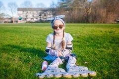 La ragazza sveglia senza dente di latte e treccia due gode di di sedersi sull'erba in pattini di rullo ed occhiali da sole immagine stock