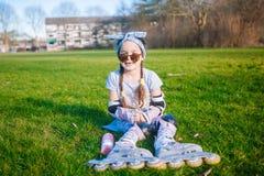 La ragazza sveglia senza dente di latte e treccia due gode di di sedersi sull'erba in pattini di rullo ed occhiali da sole immagini stock