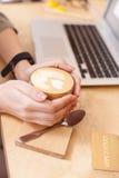 La ragazza sveglia sta bevendo il caffè caldo Immagine Stock