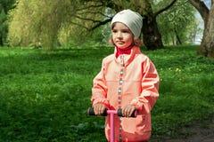 La ragazza sveglia sta camminando in un bello parco verde Fotografia Stock