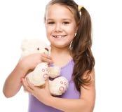 La ragazza sveglia sta spazzolando il suo orsacchiotto Immagini Stock