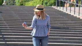 La ragazza sveglia in un cappello di paglia su una scala urbana prende una foto Una scala sull'argine di bella città è situata vi stock footage