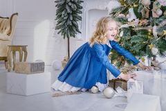 La ragazza sveglia in un umore delizioso prende la scatola di un nuovo anno con un regalo fotografie stock