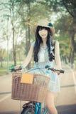 La ragazza tailandese asiatica sveglia in abbigliamento d'annata sta stando con la sua Bi fotografie stock libere da diritti