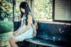 La ragazza tailandese asiatica sveglia in vestiti d'annata sta aspettando da solo Immagini Stock Libere da Diritti