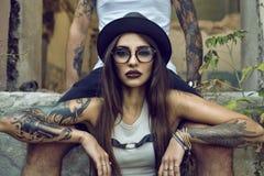 La ragazza tatuata splendida con provocatorio compone la seduta fra il suo boyfriend& x27; gambe di s nella costruzione abbandona fotografie stock