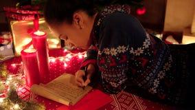 La ragazza teenager è stante e scrivente una lettera a Santa Claus Le candele brucianti e l'illuminazione sono dappertutto stock footage