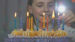 La ragazza teenager accende le candele sul dolce sul suo compleanno video d archivio
