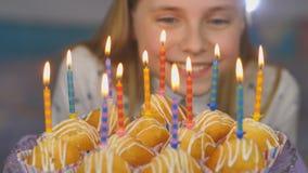 La ragazza teenager ammira le candele brucianti al dolce sul suo compleanno archivi video