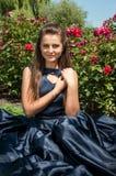 La ragazza teenager bella sta sedendosi sul prato dei fiori fotografie stock