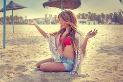 La ragazza teenager bionda si siede sulla sabbia della spiaggia Fotografia Stock Libera da Diritti