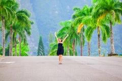 La ragazza teenager biraziale che sta nel mezzo della palma ha allineato la via Immagini Stock