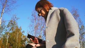 La ragazza teenager in cappotto grigio ed occhiali da sole sta cercando qualcosa in suo smartphone un giorno soleggiato archivi video