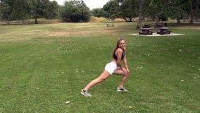 La ragazza teenager caucasica che allunga nel bianco mette la cima in cortocircuito nera al parco video d archivio