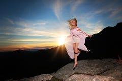 La ragazza teenager che balla su una roccia trascura nelle montagne immagine stock