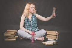 La ragazza teenager che si siede sul pavimento accanto ai libri, non vuole imparare, succo bevente e prendere un selfie sullo sma fotografie stock
