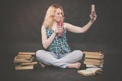 La ragazza teenager che si siede sul pavimento accanto ai libri, non vuole imparare, succo bevente e prendere un selfie sullo sma immagine stock libera da diritti