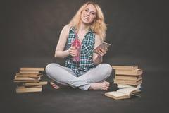 La ragazza teenager che si siede sul pavimento accanto ai libri, non vuole imparare, succo bevente e prendere un selfie sullo sma fotografia stock