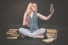 La ragazza teenager che si siede sul pavimento accanto ai libri, non vuole imparare, succo bevente e prendere un selfie sullo sma immagini stock
