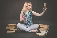 La ragazza teenager che si siede sul pavimento accanto ai libri, non vuole imparare, succo bevente e prendere un selfie sullo sma fotografia stock libera da diritti