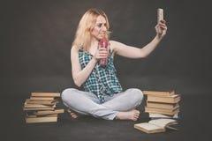 La ragazza teenager che si siede sul pavimento accanto ai libri, non vuole imparare, succo bevente e prendere un selfie sullo sma fotografie stock libere da diritti
