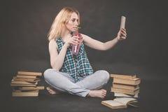 La ragazza teenager che si siede sul pavimento accanto ai libri, non vuole imparare, succo bevente e prendere un selfie sullo sma immagini stock libere da diritti