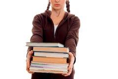 La ragazza teenager con le trecce allunga in avanti molti libri isolati su fondo bianco Immagine Stock Libera da Diritti