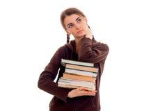 La ragazza teenager con le trecce nel rivestimento cerca e tiene molti libri Fotografie Stock Libere da Diritti