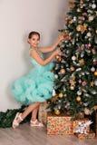 La ragazza teenager decora con l'albero del nuovo anno dei giocattoli dell'albero di Natale in vestito fertile blu immagine stock