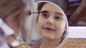 La ragazza teenager dipinge i cigli prima dello specchio dell'interno video d archivio