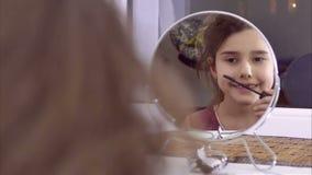 La ragazza teenager dipinge i cigli prima dello specchio dell'interno archivi video