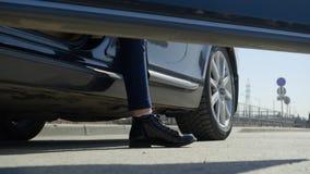La ragazza teenager esce dell'automobile e chiude la porta, gambe in primo piano degli stivali sulla strada nel sity archivi video