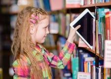 La ragazza teenager felice tira un pc della compressa fuori dagli scaffali nella biblioteca Immagini Stock