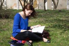 La ragazza teenager impara le lezioni all'aperto Immagine Stock