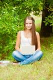La ragazza teenager lavora con il computer portatile sull'erba Fotografia Stock