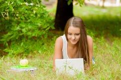 La ragazza teenager lavora con il computer portatile sull'erba Immagini Stock Libere da Diritti