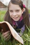 La ragazza teenager legge il libro all'aperto Fotografia Stock Libera da Diritti