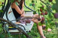 La ragazza teenager legge un libro che si siede su un'oscillazione del giardino nel giardino dell'estate fotografia stock libera da diritti