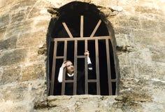 La ragazza teenager osserva dalla finestra della prigione Immagine Stock