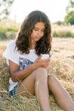 La ragazza teenager scrive gli sms nel campo Fotografie Stock Libere da Diritti