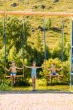 La ragazza teenager scuote i suoi bambini sulle grandi oscillazioni di estate immagini stock