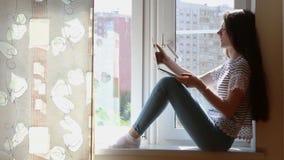 La ragazza teenager si siede il davanzale della finestra e lavora a notebooke stock footage
