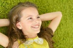 La ragazza teenager si trova sul tappeto Immagine Stock