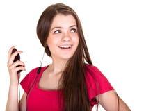 La ragazza teenager sorridente attraente ascolta musica Fotografia Stock